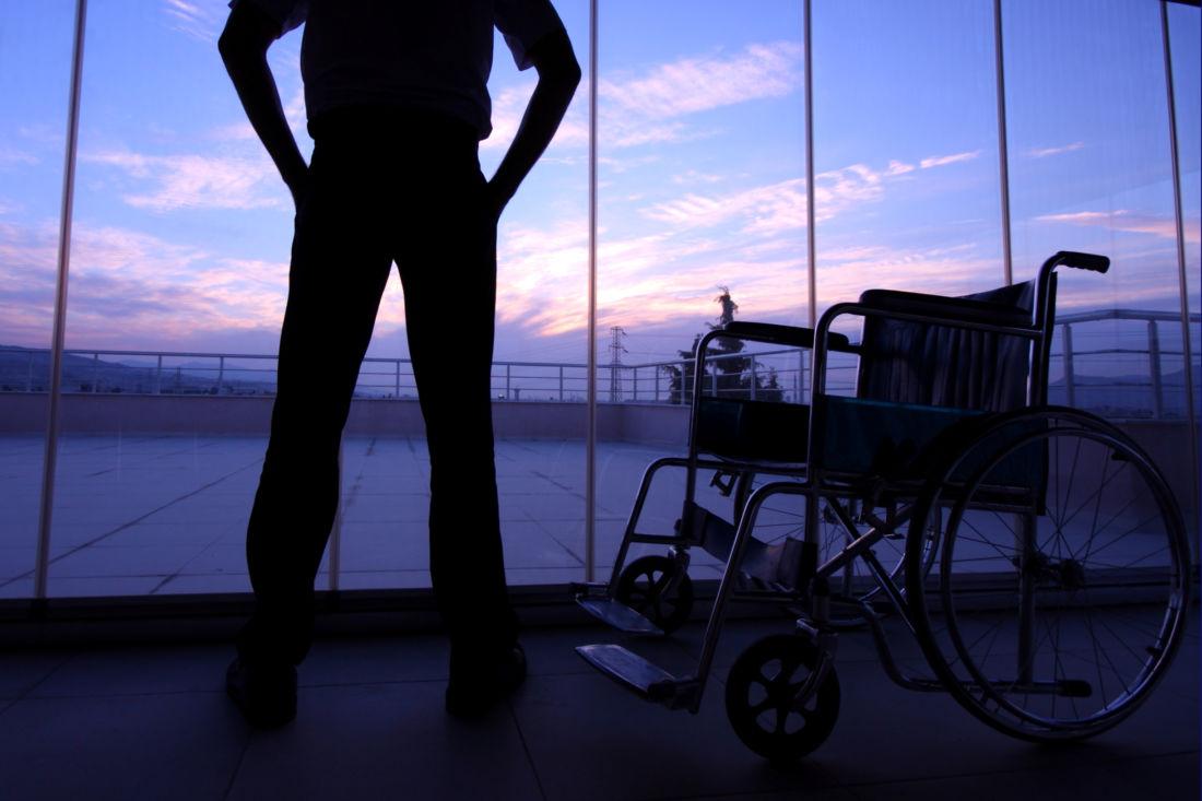 man standing near wheelchair