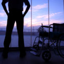 man standing near wheelchair